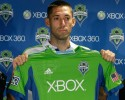 Clint Dempsey holds up a Seattle Sounders jersey after he was introduced as the newest player for the MLS soccer team, Monday, Aug. 5, 2013, in Seattle. Dempsey previously played for Tottenham Hotspur in the English Premier League. (AP Photo/Ted S. Warren)