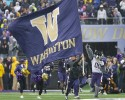 """Harry,"" the Washington Huskies mascot runs on the field with a giant flag as Washington football players come out of the tunnel for an NCAA college football game against Arizona, Saturday, Sept. 28, 2013, in Seattle."