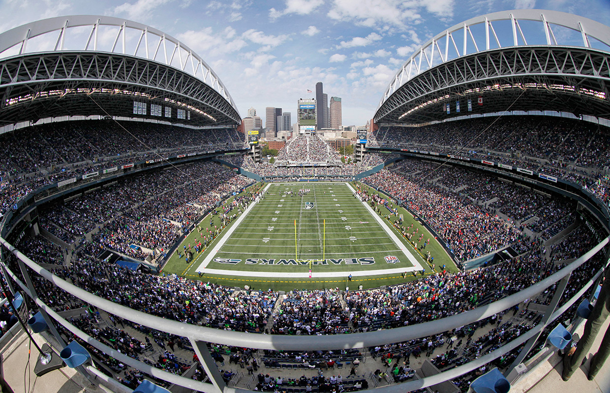 FILE - In this Oct. 2, 2011, file photo, taken with a fisheyelens, the Seattle Seahawks and Atlanta Falcons play during an NFL football game at CenturyLink Field in Seattle. Opened in 2002, the stadium's signature roof canopies and rainbow-like trusses hang over the field to protect most of the seats and trap in the crowd noise.