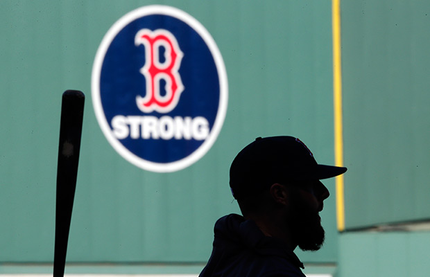 "With a ""B strong"" emblem on the Green Monster wall in honor of the Boston Marathon bombing surviviors, Boston Red Sox's Dustin Pedroia participates in team baseball practice at Fenway Park in Boston, Monday, Oct. 21, 2013. The Red Sox will face the St. Louis Cardinals in Game 1 of the World Series on Wednesday."
