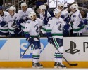 Vancouver Canucks' Jason Garrison (5) celebrates his goal alongside Alexander Edler (23) and teammates on the bench during the first period of an NHL hockey game against the San Jose Sharks on Thursday, Oct. 3, 2013, in San Jose, Calif.
