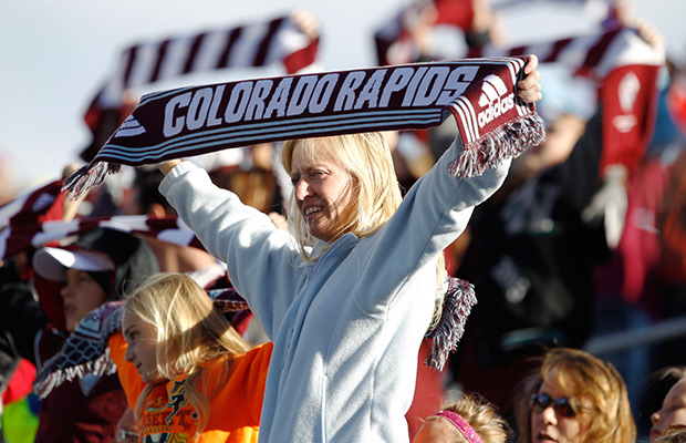 Colorado Rapids fans hoists a scarf to welcome members of the Rapids to the pitch to host the Vancouver Whitecaps in the first half of a MLS soccer game in Commerce City, Colo., on Saturday, Oct. 19, 2013.