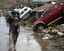 A woman walks past cars swept away by Typhoon Hayan in Tacloban, Philippines, Wednesday, Nov. 13, 2013. Typhoon Haiyan, one of the strongest storms on record, slammed into six central Philippine islands on Friday leaving a wide swath of destruction.