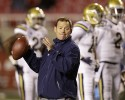 UCLA head coach Jim Mora passes the ball during practice before their NCAA college football game against Utah Thursday, Oct. 3, 2013, in Salt Lake City.