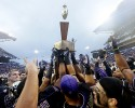 Washington players heft the Apple Cup trophy after the team beat Washington State in an NCAA college football game Friday, Nov. 29, 2013, in Seattle. Washington won the annual Apple Cup, 27-17.