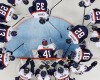 Team USA huddles around the net before their game against Slovakia during the 2014 Winter Olympics men's ice hockey game at Shayba Arena, Thursday, Feb. 13, 2014, in Sochi, Russia.