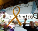"Jammi Parris, a waitress at the Blue Bird Cafe in downtown Arlington, Wash., paints a yellow ribbon and the words ""Hold on to Hope"" on the window of the cafe, Tuesday, March 25, 2014, in tribute to the victims and people missing after a massive mudslide struck Saturday, killing at least 16 people and leaving dozens missing from the communities of Oso, and Darrington, Wash."
