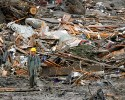A searcher walks amidst a massive pile of debris at the scene of a deadly mudslide, Thursday, March 27, 2014, in Oso, Wash.