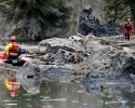 Searchers on water and land look through debris following a deadly mudslide, Tuesday, March 25, 2014, in Oso, Wash. At least 14 people were killed in the 1-square-mile slide that hit in a rural area about 55 miles northeast of Seattle on Saturday. Several people also were critically injured, and homes were destroyed.