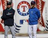 Texas Rangers pitcher Yu Darvish, right, and Seattle Mariners pitcher Hisashi Iwakuma, both of Japan, smile as they chat during batting practice before their baseball game Tuesday, April 15, 2014, in Arlington, Texas.