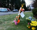 A car passes a small flower memorial, Monday, March 31, 2014, at the fire station in Darrington, Wash., at the beginning of another week of searching for victims of the massive mudslide that hit the nearby community of Oso,Wash. Crews have cleared a path through the muck and devastation wrought by Washington's deadly mudslide, making the painstaking search for victims easier. The makeshift road completed over the weekend links one side of the 300-acre debris field to the other.