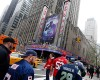 Football fans cross the street in front of Radio City Music Hall before the first round of the NFL football draft, Thursday, May 8, 2014, in New York.