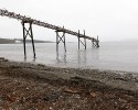 In this photo taken Oct. 23, 2012, a dilapidated structure is seen jutting out into the Strait of Georgia along the beach just south of the location of a proposed coal exporting terminal in Ferndale, Wash., just north of Bellingham, Wash. In the distance behind are an existing aluminum plant and oil refinery. The progressive college town of Bellingham is at the center of one of the fiercest environmental debates in the region: should the Northwest become a hub for exporting U.S. coal to Asia? A proposal to build one of as many as five coal terminals here has divided the town, pitting union and businesses that welcome jobs against environmentalists who worry about coal dust and greenhouse gas emissions. A trade group is running TV ads touting the projects, while numerous cities such as Seattle and Portland are opposing coal trains through their communities.