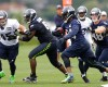 Seattle Seahawks running back Marshawn Lynch, third from left, carries the ball on the final day of NFL football training camp, Wednesday, Aug. 13, 2014, in Renton, Wash.