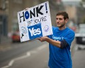 David Aguilar from Catalonia, who is visiting Scotland to support the Scottish independence referendum, holds up a placard supporting a Yes vote at passing motorists in Edinburgh, Scotland, Thursday, Sept. 18, 2014. Polls have opened across Scotland in a referendum that will decide whether the country leaves its 307-year-old union with England and becomes an independent state.