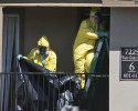 Hazardous material cleaners prepare to hang black plastic outside the apartment in Dallas, Friday, Oct. 3, 2014, where Thomas Eric Duncan, the Ebola patient who traveled from Liberia to Dallas stayed last week. The crew is expected to remove items including towels and bed sheets used by Duncan, who is being treated at an isolation unit at a Dallas hospital. The family living there has been confined under armed guard while being monitored by health officials.