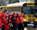 People dressed in the school colors of red and white cheer and wave as school buses carrying students on their return to Marysville-Pilchuck High School drive past Monday, Nov. 3, 2014, in Marysville, Wash. After the shock from the Oct. 24 shooting there that left four students dead, including the shooter, and two students still in a Seattle hospital, administrators and teachers hope to transition to a new routine. The day was scheduled to begin with a morning assembly. Lunch is in the gym because the cafeteria where the shooting took place remains closed.