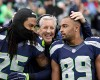Seattle Seahawks head coach Pete Carroll, center, throws his arms around Richard Sherman (25) and Doug Baldwin before an NFL football game against the Arizona Cardinals, Sunday, Nov. 23, 2014, in Seattle.