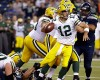 Green Bay Packers quarterback Aaron Rodgers (12) is pressured by Seattle Seahawks' Michael Bennett, lower left, late in the second half of an NFL football game, Thursday, Sept. 4, 2014, in Seattle. The Seahawks beat the Packers 36-16.