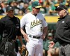 Oakland Athletics manager Bob Melvin talks with umpires Adam Hamari, left, and Bill Miller, right, after the Texas Rangers' Carlos Corporan was given a base after being hit by a pitch from A's starter Kendall Graveman in the second inning of their baseball game Thursday, April 9, 2015, in Oakland, Calif. Texas won the game 10-1.