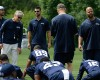 Seattle Seahawks defensive coordinator Kris Richard, right, stands with head coach Pete Carroll, second from left, and other team personnel as players stretch at the start of an organized team activity Tuesday, May 26, 2015, in Renton, Wash.