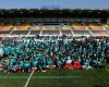 Miami Dolphins players and cheerleaders pose for a group picture with London schoolchildren during a training session Allianz Park in London, Friday Oct. 2, 2015. The Dolphins are preparing for an NFL football game against the New York Jets at London's Wembley stadium on Sunday. (AP Photo/Tim Ireland)