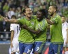 Seattle Sounders' Nelson Valdez, left, celebrates with teammates Obafemi Martins, center, and Clint Dempsey, right, after Valdez scored a goal against the Los Angeles Galaxy in the first half of an MLS soccer western conference knockout round playoff match, Wednesday, Oct. 28, 2015, in Seattle. (AP Photo/Ted S. Warren)