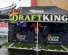 FILE - In this Oct. 25, 2015, photo, workers set up a DraftKings promotions tent in the parking lot of Gillette Stadium, in Foxborough, Mass., before an NFL football game between the New England Patriots and New York Jets. New York's attorney general on Tuesday, Nov. 10, 2015, ordered the daily fantasy sports companies DraftKings and FanDuel to stop accepting bets in the state, saying their operations amount to illegal gambling. (AP Photo/Charles Krupa, File)